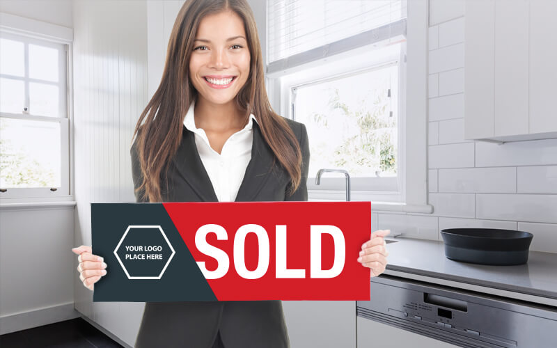 A Female Real Estate Agent In A Kitchen Holding A Sold Sign